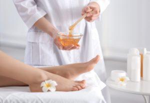 woman applying wax to feet
