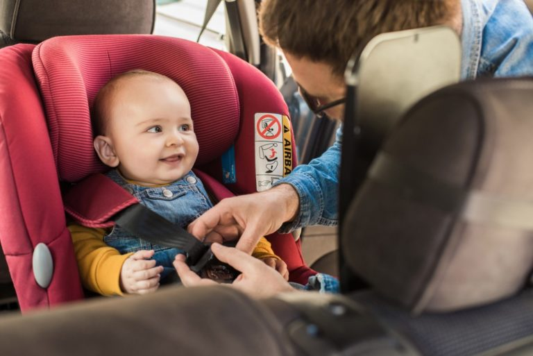 infant being secured in booster seat