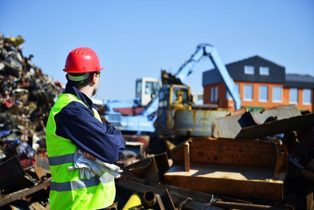 Worker at a junk yard of metal scraps