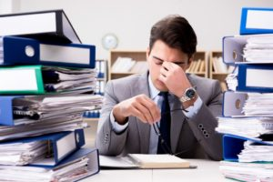 tired businessman with piles of paperwork