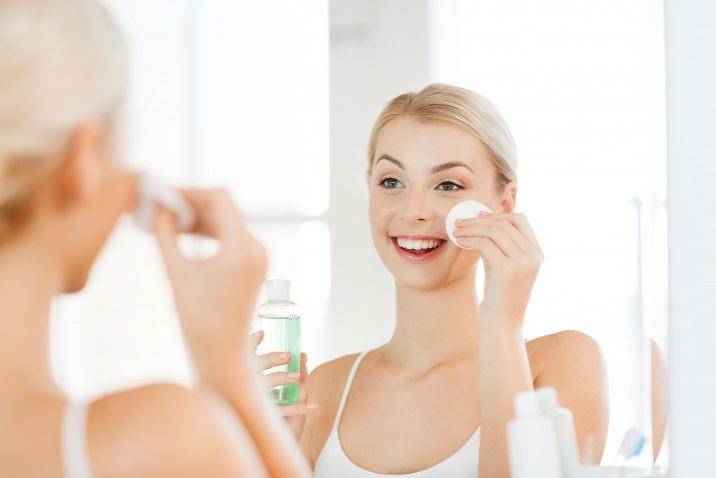 smiling young woman applying toner on her face