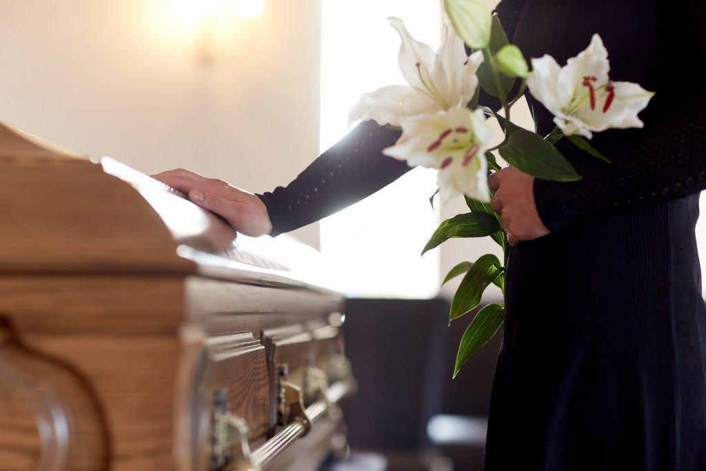 Woman holding casket and white flowers