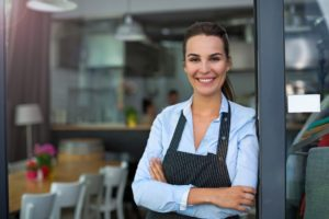 Restaurant owner. Standing in front of her shop