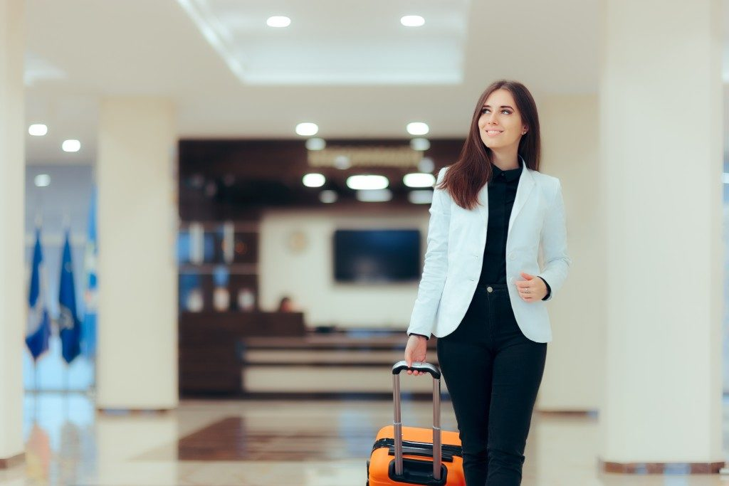 Woman carrying her suitcase in the airport