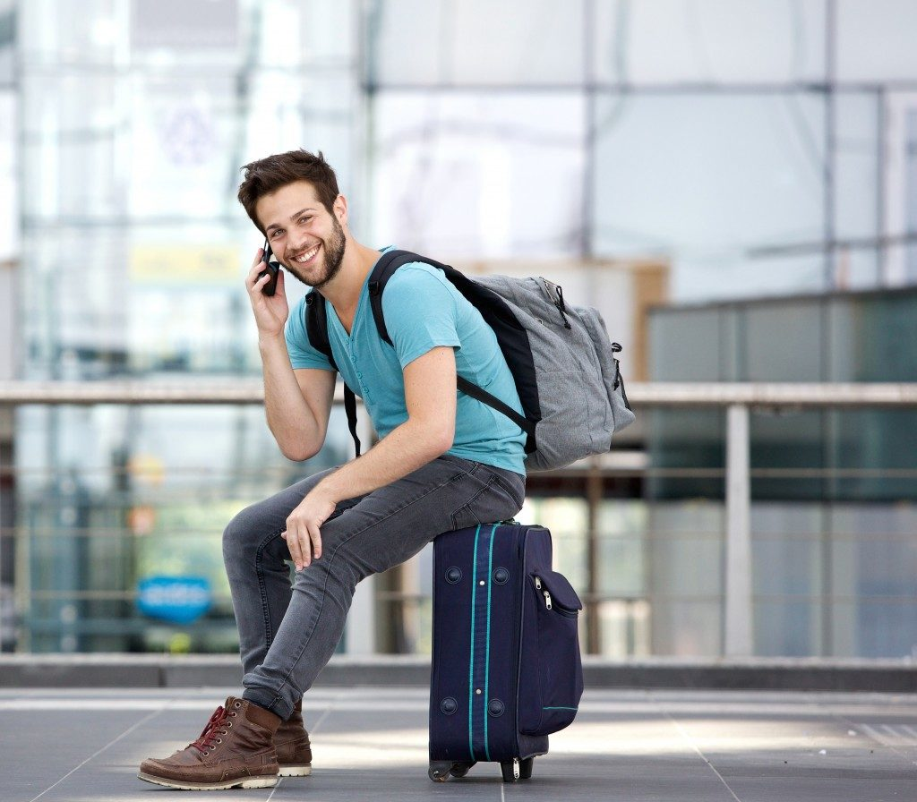 Man sitting on suitcase and calling by cellphone at airport
