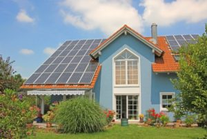 modern new built house and garden, rooftop with solar cells, blue front with lattice window.