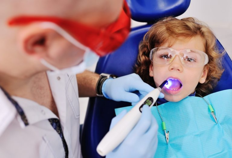 young kid having his teeth examined