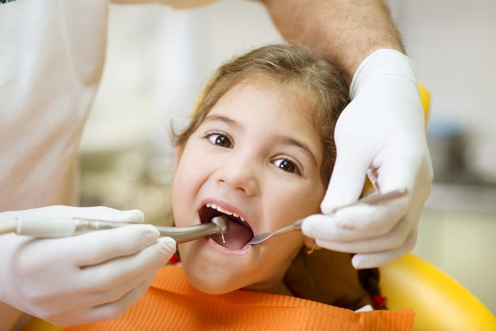 young girl having her teeth cleaned