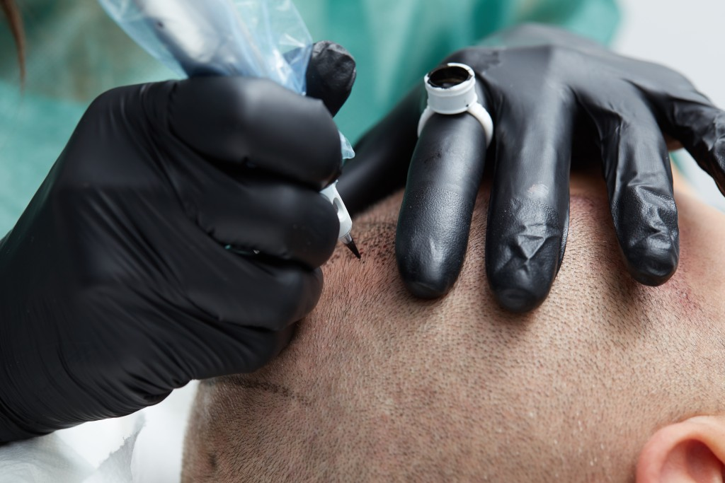 Cosmetologist making permanent makeup on man head