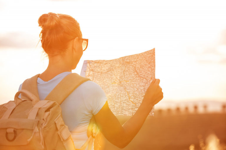 Back side of traveler girl searching right direction on map