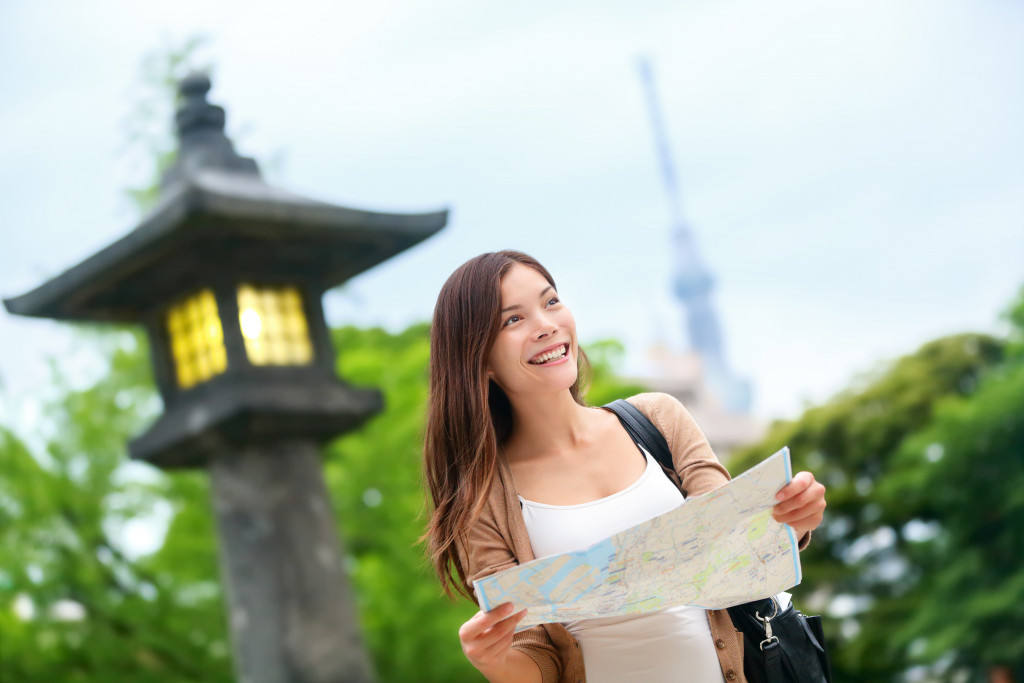 Woman with map searching for directions with the Tokyo Skytree tower in the background