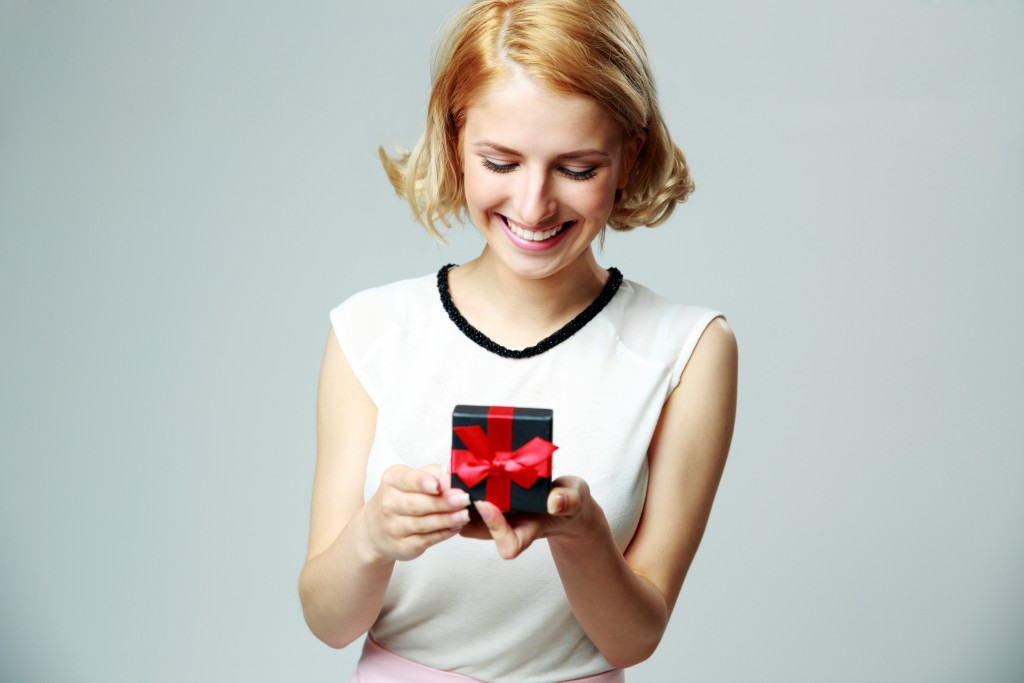 smiling woman holding a jewelry gift box
