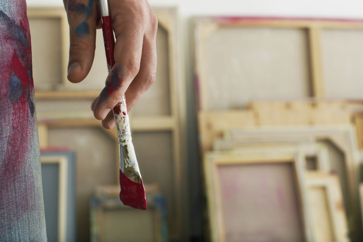 close up photo of painter holding a paintbrush
