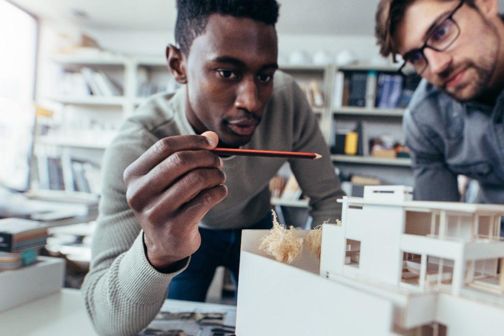men looking at a pencil